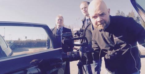 Viimeinen tarkistus autoon rigatuista kameroista. Taustalla Antti Rinne ja toimittaja Esa Juntunen.